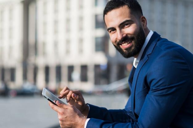 Vista lateral homem usando celular