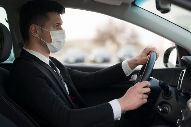 Vista lateral homem vestindo máscara durante a condução