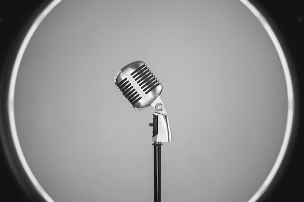 Vista lateral horizontal do microfone metálico do estilo antigo dentro de uma luz profissional do círculo. conceito de música retrô oldies.