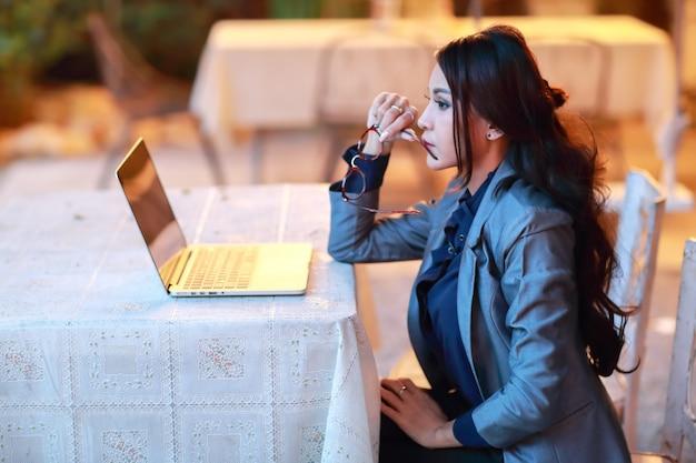 Vista lateral, imagem, de, bonito, asiático, executiva, com, óculos, trabalhando, e, pensando, ligado, computador laptop