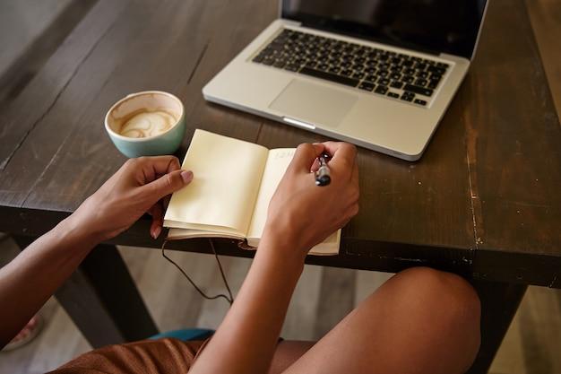 Vista lateral interna de mãos femininas com caneta e caderno, escrevendo anotações enquanto toma uma xícara de café, usando um laptop moderno para trabalho remoto