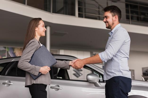 Vista lateral jovem apertando as mãos com o negociante de carro