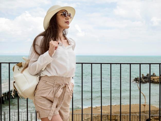 Vista lateral jovem fêmea com mochila