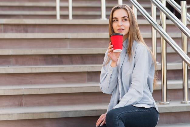 Vista lateral, jovem, femininas, bebendo café, ao ar livre