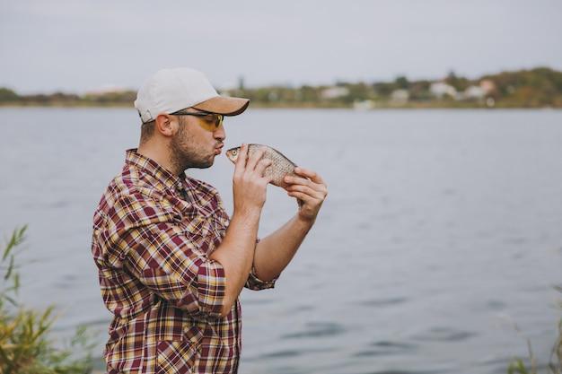 Vista lateral jovem homem com a barba por fazer em camisa quadriculada, boné e óculos de sol pegou um peixe e quer beijá-lo na margem do lago no fundo da água, arbustos e juncos. estilo de vida, conceito de lazer de pescador