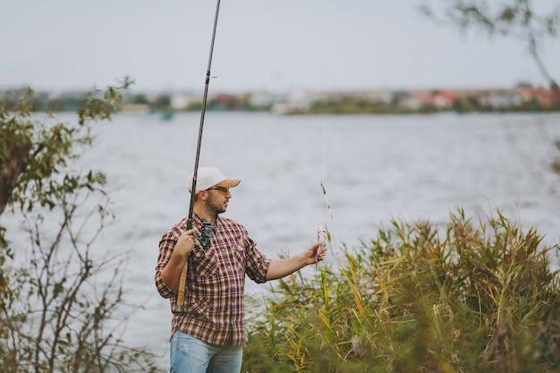 Vista lateral jovem homem com a barba por fazer em camisa xadrez, boné, óculos de sol puxou a vara de pescar e detém peixes capturados na margem do lago perto de arbustos e juncos. estilo de vida, recreação, conceito de lazer de pescador