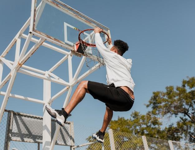 Vista lateral jovem jogando basquete
