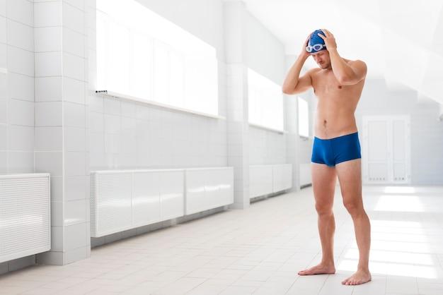 Vista lateral jovem macho na bacia com tampa e óculos de proteção
