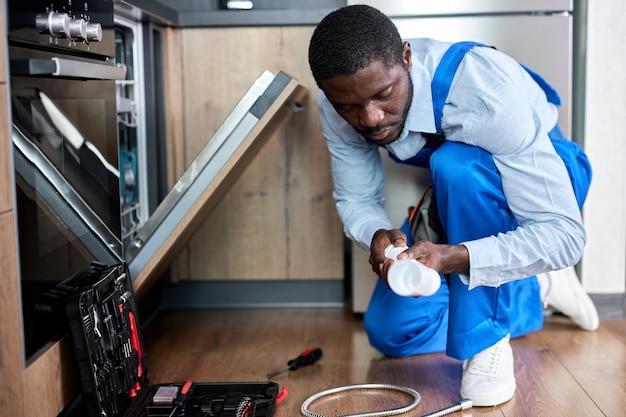 Vista lateral jovem negro afro faz-tudo reparador consertando a máquina de lavar louça, trocando o sifão, vestindo macacão azul workwear. faz-tudo profissional confiante, focado no trabalho sozinho, na cozinha