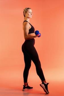 Vista lateral jovem treinamento feminino com pesos