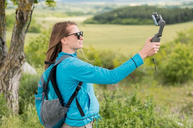 Vista lateral jovem viajante tomando uma selfie ao ar livre
