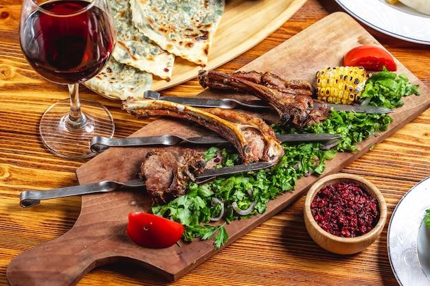 Vista lateral kebab de cordeiro costelas de cordeiro grelhadas com verdes de tomate alface cebola roxa milho grelhado bérberis secas e copo de vinho tinto em cima da mesa
