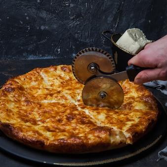 Vista lateral khachapuri com queijo sulguni e faca de corte de pizza e mão humana em placa escura