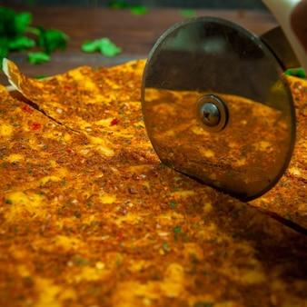 Vista lateral lahmacun com faca de corte de pizza e salsa