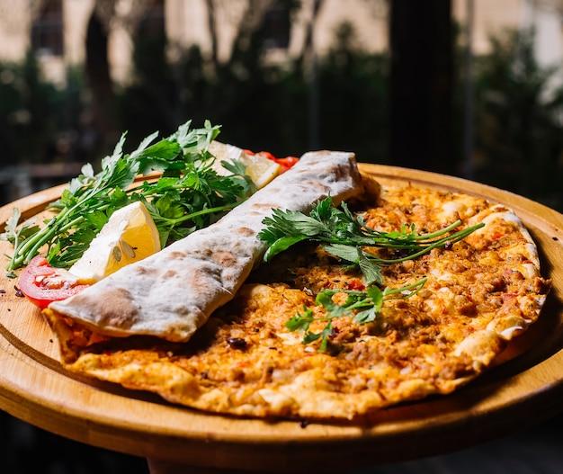 Vista lateral lahmajun com verduras de carne moída e limões em uma bandeja