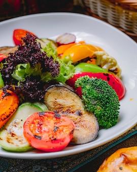 Vista lateral legumes grelhados berinjela abóbora pimentão alface tomate couve-flor e rabanete em um prato