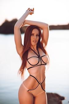 Vista lateral, linda garota com seios grandes e bunda sexy em trajes de banho tomando banho de sol na praia de areia preta.