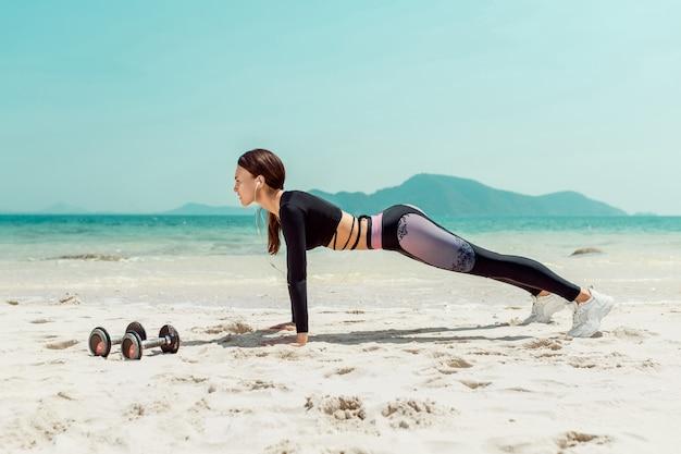 Vista lateral linda mulher desportiva na praia de posição de prancha. esporte . phuket. tailândia