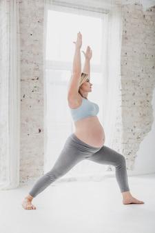 Vista lateral linda mulher grávida alongamento