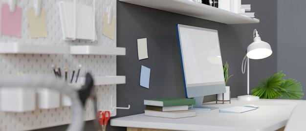 Vista lateral local de trabalho criativo e elegante em apartamento com parede cinza de maquete de tela em branco de computador