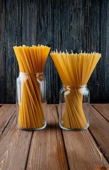 Vista lateral macarrão bucatini e espaguete em uma jarra com fundo de madeira