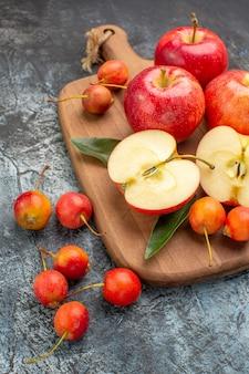 Vista lateral, maçãs, cerejas, maçãs vermelhas, com folhas na placa de madeira