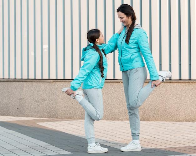 Vista lateral mãe e filha alongamento