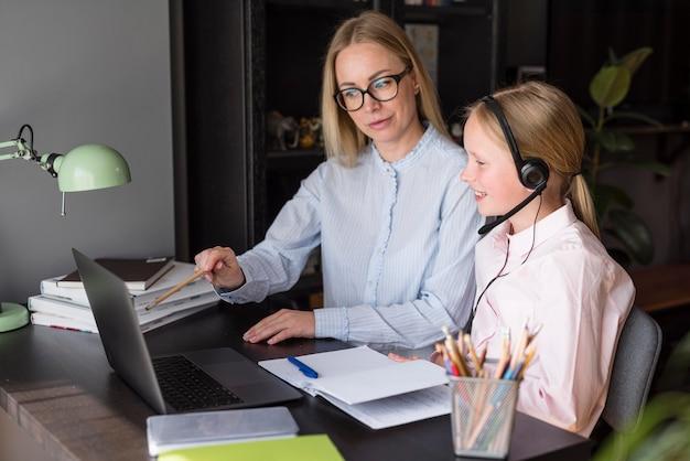 Vista lateral mãe e filha participando de uma aula on-line