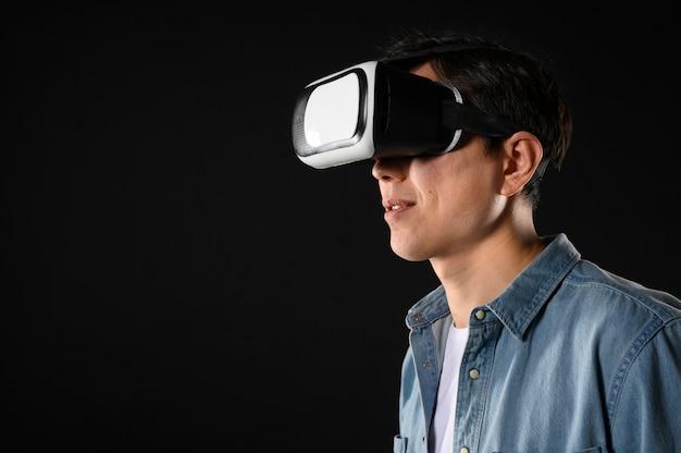 Vista lateral masculina com fone de ouvido de realidade virtual