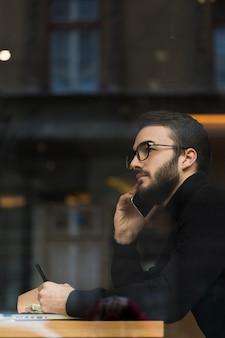 Vista lateral masculina falando por telefone