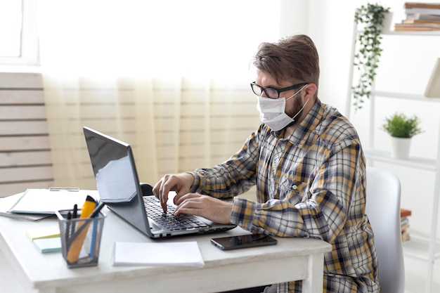Vista lateral masculino trabalhando em casa no laptop