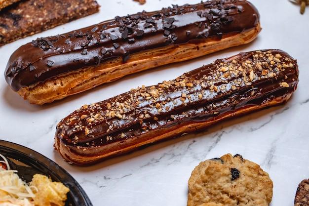 Vista lateral, massa eclair choux, recheada com creme e coberta com cobertura de chocolate