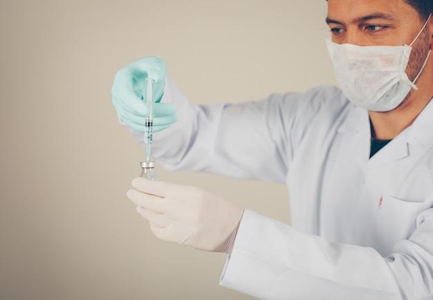Vista lateral médico com luvas e máscara, preenchendo a seringa em um frasco. horizontal
