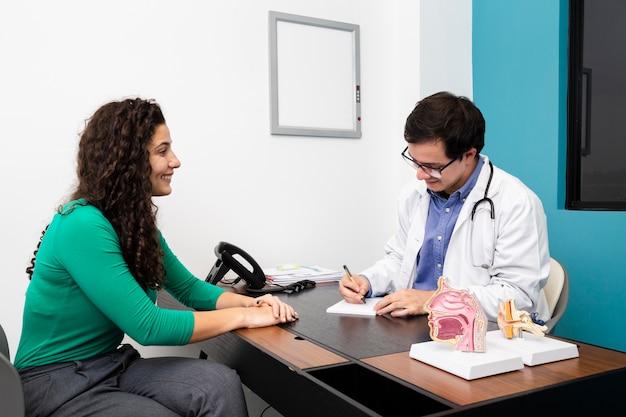 Vista lateral médico escrevendo uma receita