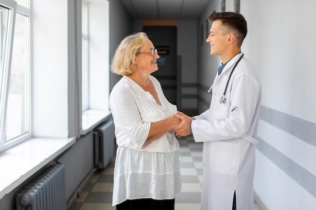 Vista lateral médico segurando as mãos do paciente