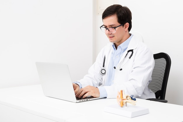 Vista lateral médico trabalhando no laptop