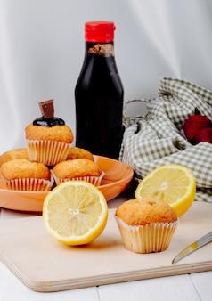 Vista lateral meio limão com muffins no quadro