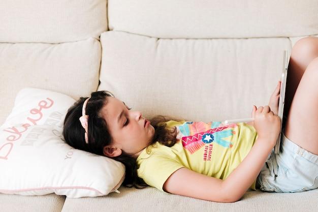 Vista lateral menina com tablet sentado no sofá