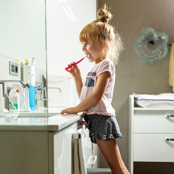 Vista lateral menina escovando os dentes no banheiro