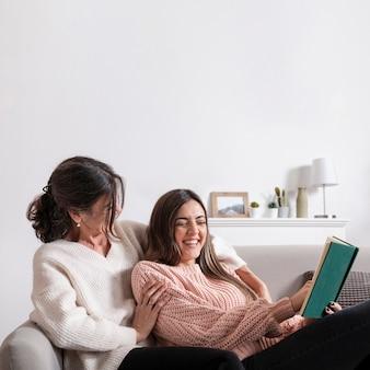 Vista lateral menina lendo para mãe