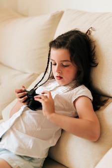 Vista lateral menina olhando fotos na câmera