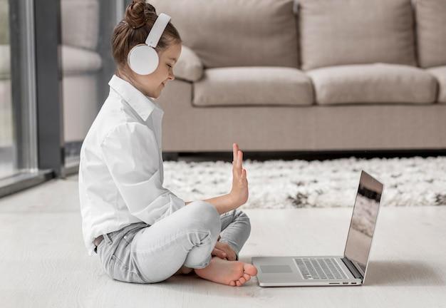 Vista lateral menina ouvindo seu professor através de fones de ouvido
