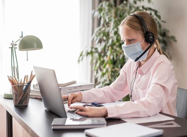 Vista lateral menina participando de aulas on-line em casa