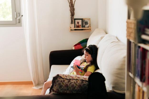 Vista lateral menina sentada no sofá com suco
