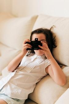 Vista lateral menina sentada no sofá e tirar fotos