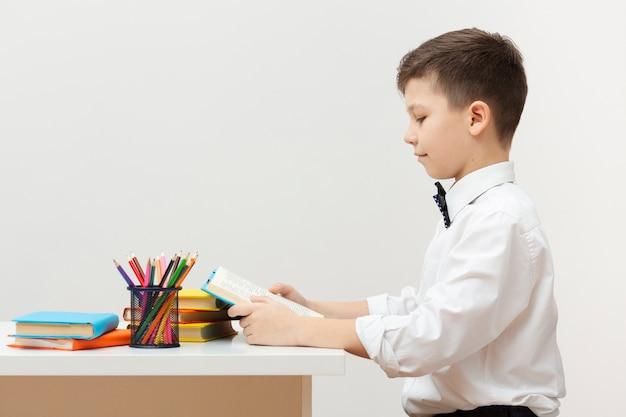 Vista lateral, menino jovem, leitura