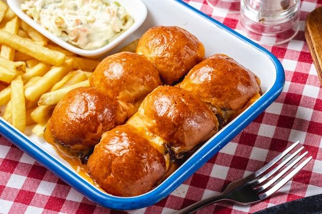 Vista lateral mini hambúrgueres com salada de queijo patty de carne e batatas fritas em cima da mesa