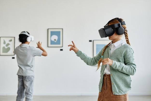 Vista lateral mínima para uma linda garota usando fone de ouvido vr na galeria de arte enquanto desfruta de uma experiência imersiva, copie o espaço