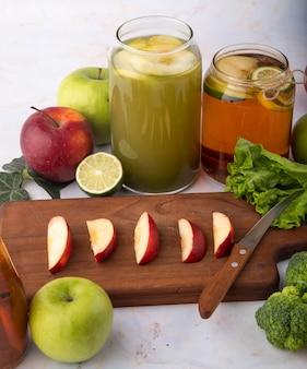 Vista lateral, misture maçã, suco de maçã fresco, brocoli, chá de limão fatiado, maçã vermelha em uma placa verde maçã fatia de limão e alface folha na superfície branca