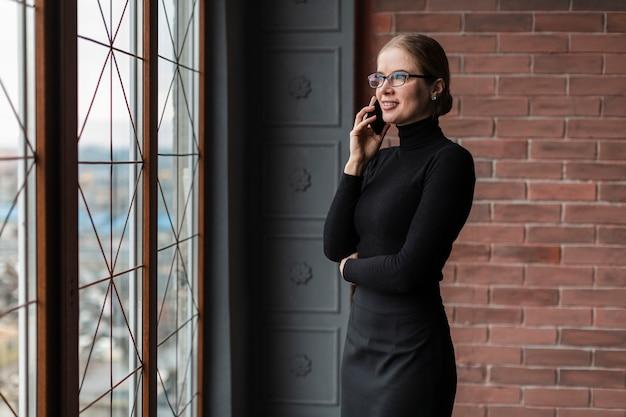 Vista lateral moderna fêmea falando no celular